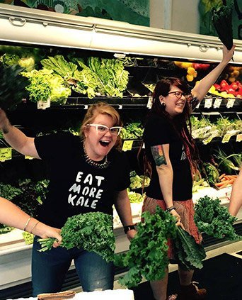 "Two people in a grocery stores enthusasitically market kale. One wears a shirt that says ""Eat More Kale."" They love it!"